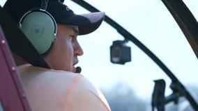 Il pilota dell'elicottero mette sopra la cuffia avricolare per i negoziati con lo spedizioniere Richiede il permesso di decollo archivi video