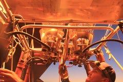 Il pilota della mongolfiera controlla il bruciatore della fiamma Immagine Stock