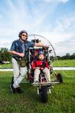 Il pilota ed i bambini non identificati con la preparazione del paragider decollano Fotografia Stock Libera da Diritti
