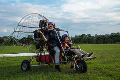Il pilota ed i bambini non identificati con la preparazione del paragider decollano Fotografie Stock Libere da Diritti