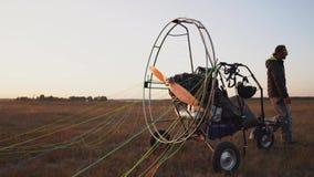 Il pilota maschio di un aliante del motore fissa il paracadute al corpo dell'aliante in preparazione del volo e del controllo archivi video
