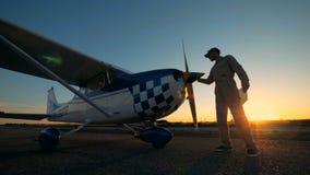 Il pilota maschio pulisce l'elica di un aereo, vista laterale video d archivio