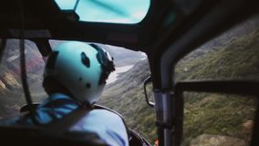 Il pilota nel volo della cabina dell'elicottero in montagne video d archivio
