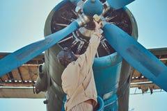 Il pilota o il meccanico in un ingranaggio pieno di volo controlla l'elica dei suoi retro ærei militari prima di un volo immagini stock libere da diritti