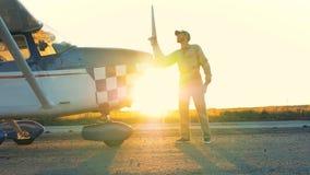 Il pilota pulisce l'elica dell'aeroplano, vista laterale video d archivio