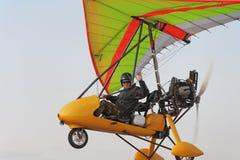 Il pilota vola su un appendere-aliante giallo del motore Fotografia Stock Libera da Diritti