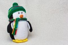 Il pinguino ha farcito il giocattolo sullo spazio lanuginoso bianco della copia del fondo Immagini Stock