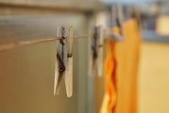 Il piolo di legno della molletta da bucato che appende sulla corda del balcone come simbolo del lavaggio copre a casa Immagini Stock