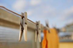 Il piolo di legno della molletta da bucato che appende sulla corda del balcone come simbolo del lavaggio copre a casa Fotografia Stock