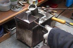 Il piombo fuso di versamento unisce in lega in una muffa workshop Fotografia Stock