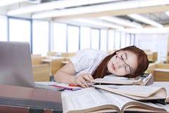 Il pisolino dello studente nella classe e si appoggia il libro Fotografia Stock Libera da Diritti