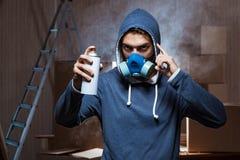 Il pittore dei graffiti nella stanza affumicata scura Fotografia Stock