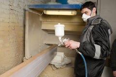 Il pittore del carpentiere dipinge il bordo della mobilia con una pistola a spruzzo sopra Immagine Stock