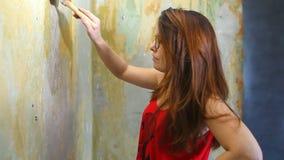 Il pittore della donna dipinge il lavoro della riparazione della parete in archivi video