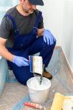 Il pittore dipinge la parete con la tinta di bianco Fotografia Stock