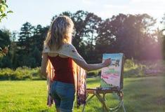Il pittore dipinge le pitture a olio nel giardino al tramonto fotografia stock libera da diritti