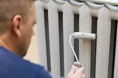 Il pittore dipinge il radiatore del ghisa fotografia stock