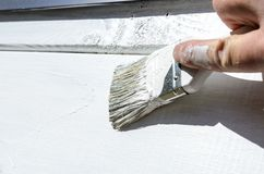 Il pittore dipinge un pezzo di parete di legno con una piccola spazzola e una pittura bianca fotografia stock libera da diritti
