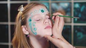 Il pittore fa la forma della farfalla al fronte del ` s della ragazza video d archivio