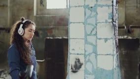 Il pittore femminile dei graffiti sta creando l'immagine astratta sulla colonna in vecchio magazzino nocivo e sta ascoltando musi stock footage