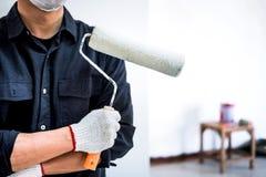 Il pittore maschio con il braccio ha attraversato il rullo di pittura della tenuta, wor interno immagine stock libera da diritti