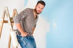 Il pittore in pittura ha schizzato la camicia che dipinge una parete Immagini Stock Libere da Diritti