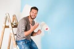 Il pittore in pittura ha schizzato la camicia che dipinge una parete Immagini Stock