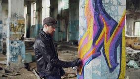 Il pittore professionista dei graffiti sta creando l'immagine astratta grande sulla costruzione abbandonata della colonna interno archivi video