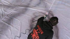 Il pittore superiore di vista in abiti da lavoro estrae la mano con lo spruzzatore archivi video