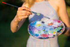 Il pittore tiene una spazzola e una tavolozza in pittura ad olio, fine su immagine stock
