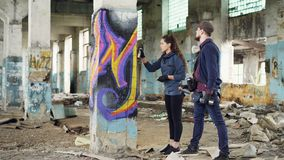 Il pittore urbano sta spiegando alla giovane donna attraente come dipingere i graffiti, essi sta stando accanto alla colonna in n archivi video