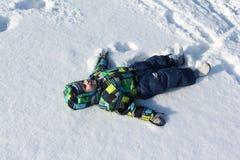 Il poco boywith una menzogne di menzogne di sorriso sulla neve Immagini Stock
