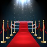 Il podio con tappeto rosso e la barriera rope nell'incandescenza dei riflettori fotografia stock