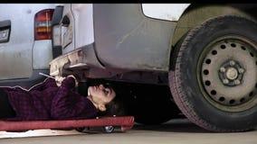 Il podlazit del meccanico della ragazza sotto l'automobile per la sua riparazione archivi video