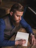 Il poeta barbuto abile sta notando i suoi ides immagine stock