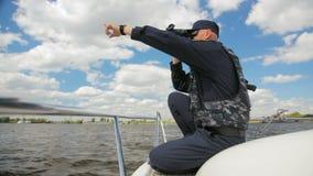Il poliziotto dell'acqua si siede sul fiume del monitoraggio del motoscafo tramite il binocolo stock footage