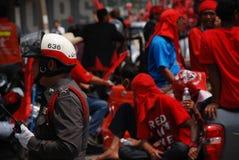 Il poliziotto riflette la protesta rossa della camicia immagine stock libera da diritti