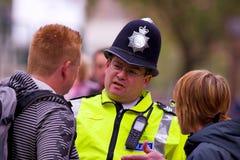 Il poliziotto sta consigliando la gente Fotografia Stock
