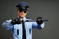 Il poliziotto tiene il manganello Fotografia Stock