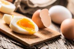 Il pollo bollito o crudo del primo piano eggs sul bordo di legno Fotografia Stock Libera da Diritti