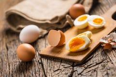 Il pollo bollito o crudo del primo piano eggs sul bordo di legno Fotografia Stock