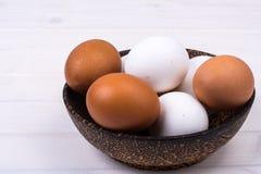 Il pollo colorato eggs in ciotola di legno sui bordi bianchi Immagine Stock