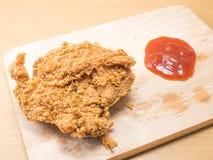 Il pollo fritto su uno spezzettamento vasto con un sause del pomodoro ha messo su un fondo di legno immagine stock libera da diritti