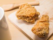 Il pollo fritto su uno spezzettamento vasto con un vetro ha messo su un fondo di legno immagine stock