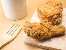Il pollo fritto su uno spezzettamento vasto con un vetro ha messo su un fondo di legno fotografia stock libera da diritti