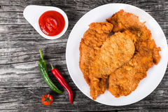 Il pollo fritto taglia su un piatto bianco, vista superiore immagini stock libere da diritti