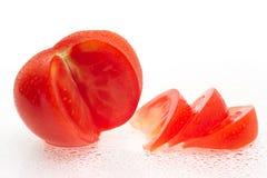 Il pomodoro fresco fruttifica con le fette e le gocce dell'acqua. Fotografia Stock