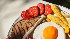Il pomodoro nell'insieme combinato della bistecca di braciola di maiale ha uovo fritto, cereale, b verde immagine stock