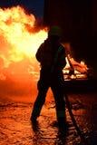 Il pompiere annaffia un fuoco in mezzo di forti fiamme Immagini Stock