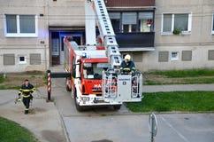 Il pompiere comincia al uprise nel canestro telescopico dell'asta del camion dei vigili del fuoco, caseggiato nel fondo Immagine Stock